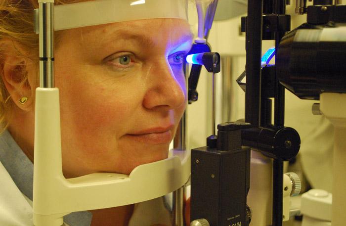 blauw licht van medisch apparaat schijnt op oog vrouw