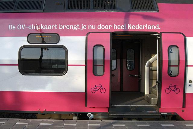 roze-witte trein met fietsingang geopend. Tekst erboven: De ov-chipkaart brengt je nu door heel Nederland