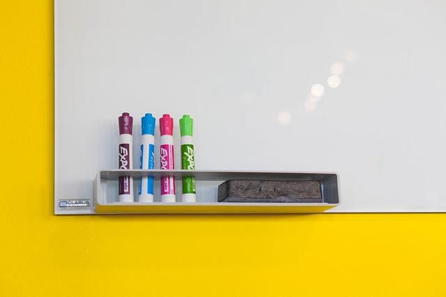 gele wand met white board, daarop ene rijtje met 4 gekleurde stiften.