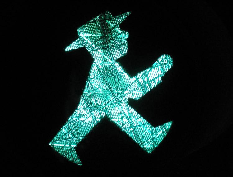zwart vlak met groen figuurtje met hoed, bekend als ampelmaennchen.