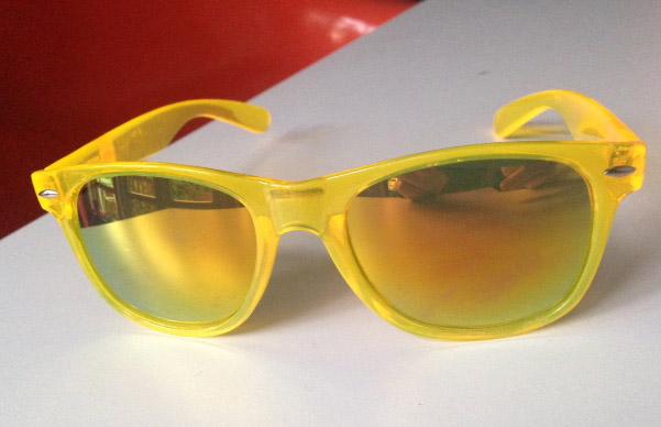 gele zonnebril met spiegelende glazen op oranje-wit vlak