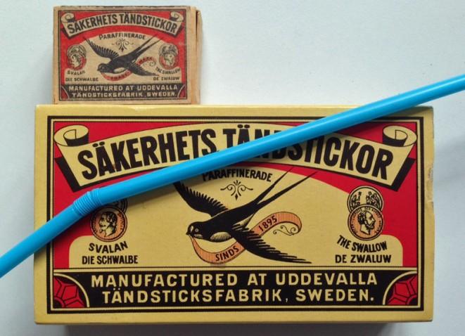 grote en kleine lucifersdoos, merk Sakerhets Tandstickor (met zwaluw). En blauw rietje er bovenop.