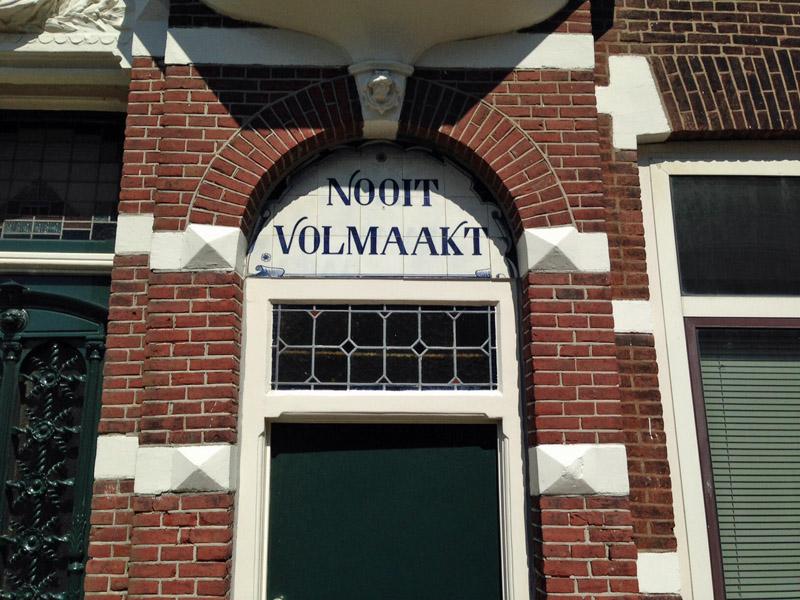 toegangsdeur van historisch huis, met tekst in tegels erboven: Nooit Volmaakt.