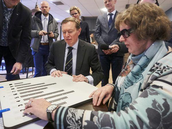 Minister Bruins en Marianne Huijben bekijken samen de stemmal voor de verkiezingen