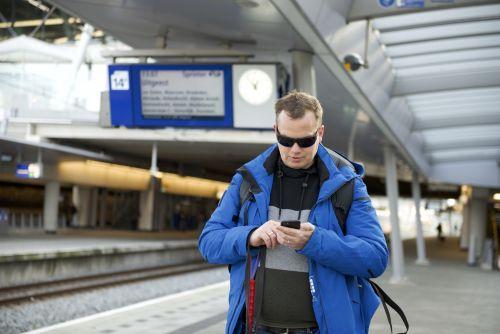 Blinde reiziger bekijkt perronbord via zijn app