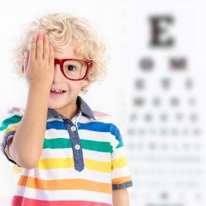 Kind met hand voor zijn oog naast een wazige letterkaart
