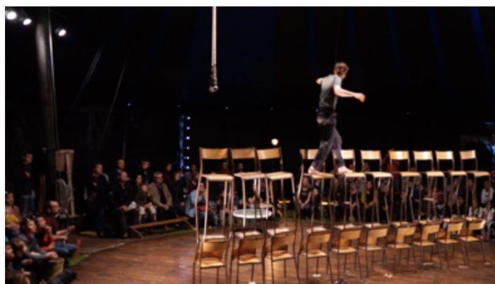 Publiek kijkt naar een circusartiest die zich over een gebouwde toren van stoelen maneuvreert