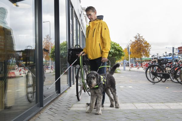 Man met stok en geleidehond komt aan bij ingang station