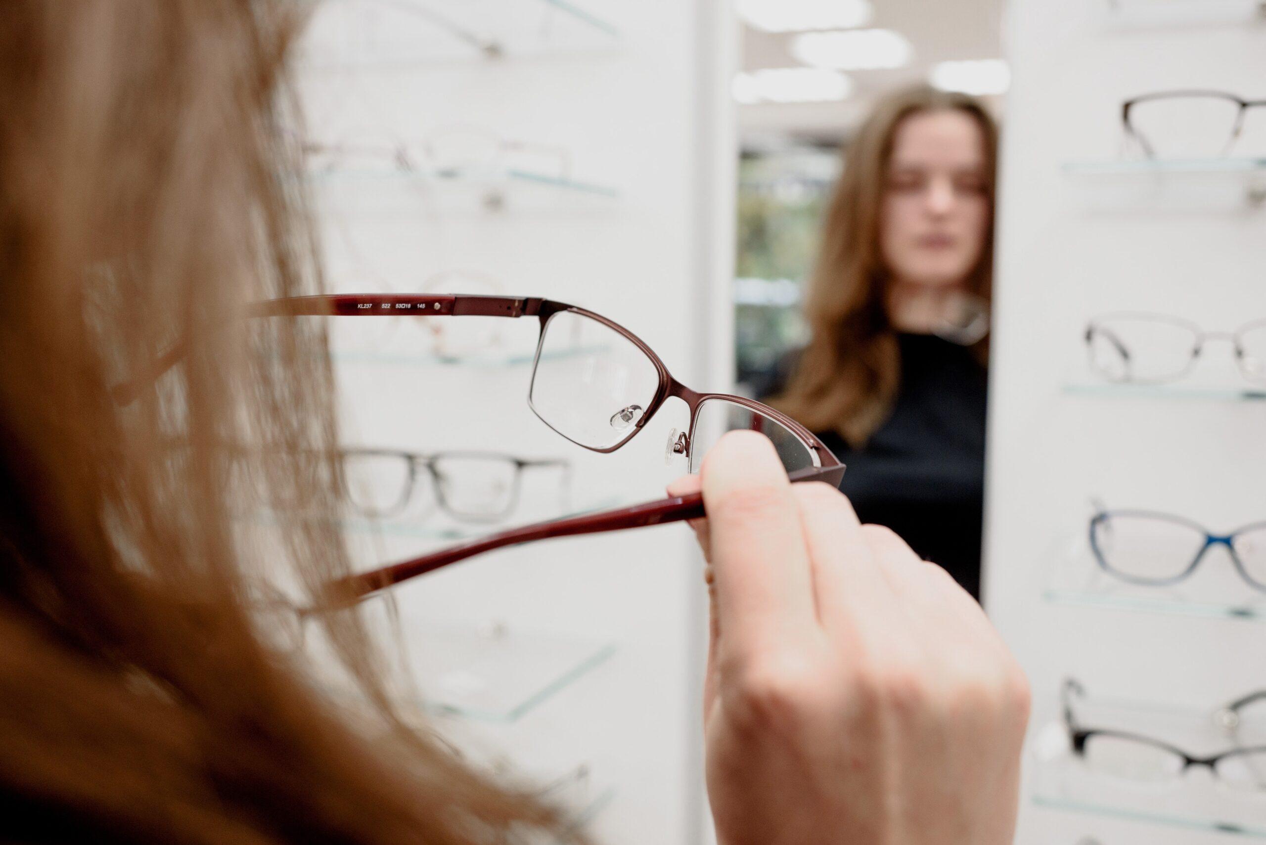 Bijziende vrouw kijkt bij de opticien in de spiegel