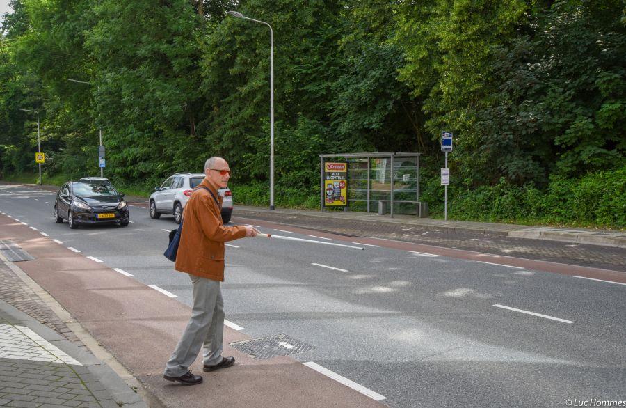 Man met stok steekt straat over